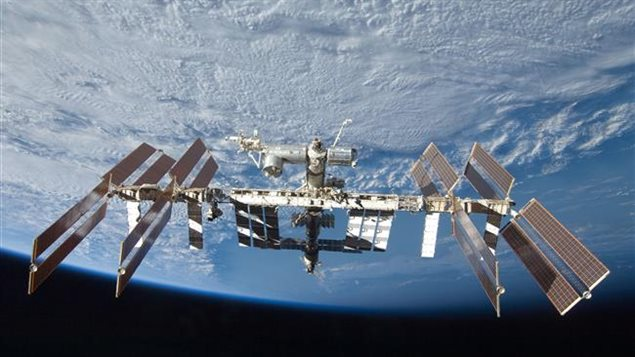 2009-09-08 - The International Space Station (ISS) from the vantage point of a Space Shuttle Discovery observer. At this stage, the ISS is near completion. Visible is Canadarm2, *waving* from the top-most perch of the Station