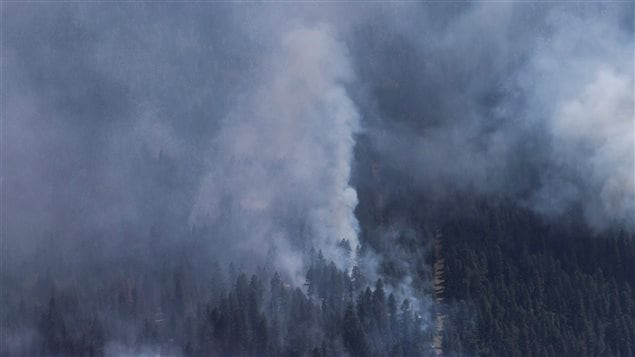 A wildfire is seen from a Canadian Forces Chinook helicopter as Prime Minister Justin Trudeau views areas affected by wildfire near Williams Lake, B.C., on Monday July 31, 2017. British Columbia is facing its worst wildfire season as flames scorch more than one million hectares of land and costs rise to deal with the devastation.