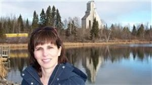 Janice Martell shown in front of the old McIntyre Mine headframe in Schumacher, northern Ontario. She's been leading the campaign to document connection fo McIntyre powder to high incidence of miner brain damage