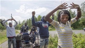 A group of asylum seekers raise their hands as they approach RCMP officers while crossing the Canadian border Friday, August 4, 2017 from Champlain, N.Y.