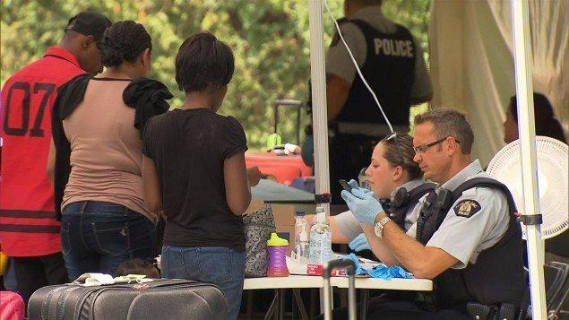 Refugiados haitianos en la frontera canadiense son recibidos por agentes de la Policía Federal.