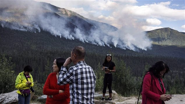 People gather on the side of the highway to watch a forest fire burn near Revelstoke B.C. on Saturday August 19, 2017. Restrictions on travel to British Columbia's backcountry and bans on campfires were lifted in some parts of the province on Wednesday as improved conditions lowered the wildfire risk.