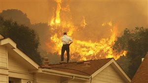 Un homme regarde le feu qui s'approche de sa maison dans les Rocheuses canadiennes plus tôt cet été.