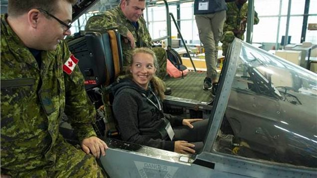 A participant of the Women in Force programme sits in a CF-18 Hornet and chats with a military members about the jet at the 400 Squadron in Canadian Forces Base (CFB) Borden, Ontario on August 17, 2017. In the Canadian Forces, in addition to dozens of other options, from, doctor, lawyer, vehicle mechanic etc, women can choose tobecome front line combattnats including fighter jet pilots.