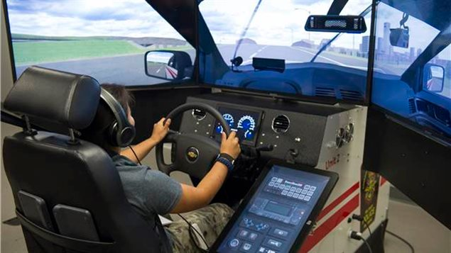 A participant of the Women in Force program tries out the driving simulator at the Canadian Forces Military Police Academy (CFMPA) Canadian Forces Base (CFB) Borden, Ontario on August 16, 2017.