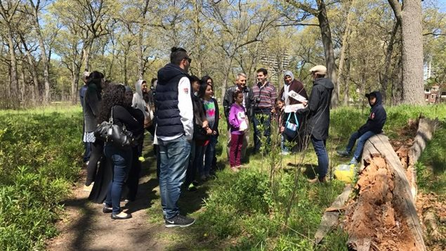 Volunteers and guides show Syrian refugees around Toronto's High Park Nature Centre.