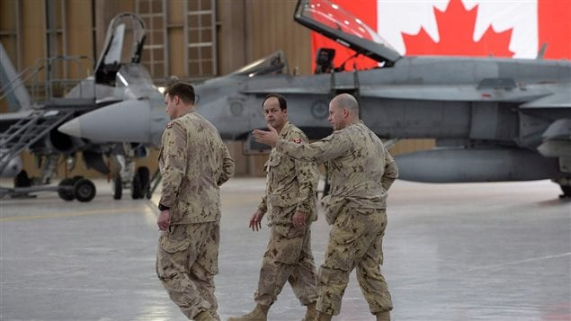 Chief of the Defence Staff Tom Lawson (centre) walks past two F-18 fighter jets as he talks with fellow members of the Canadian Forces at Camp Patrice Vincent in Kuwait on Sunday, May 3, 2015. Three retired air force generals say buying used fighter jets from Australia is a much better plan for Canada than purchasing new Super Hornets from Boeing.