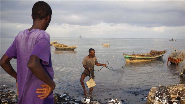 Un pêcheur ramène son bateau à la rive en prévision du passage de l'ouragan. Photo : Associated Press/Dieu Nalio Chery