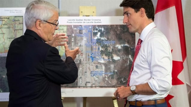 Prime Minister Justin Trudeau (right) received a briefing on the refugee installations at the Lacolle border crossing by Transport Minister Marc Garneau before meeting with the Intergovernmental Task Force on Irregular Migration on Aug 23/17. Many people say it was Trudeau's tweet that Canada welcomes everyone that caused the spike in illegal crossing and asylum claims.