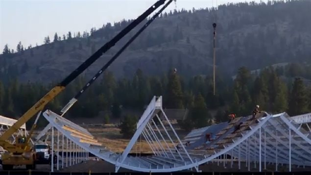 Video image of CHIME under construction. Cranes and workers show relative size of the segments and arrays located in the hills around Penticton British Columbia, in the Okanagan Valley.
