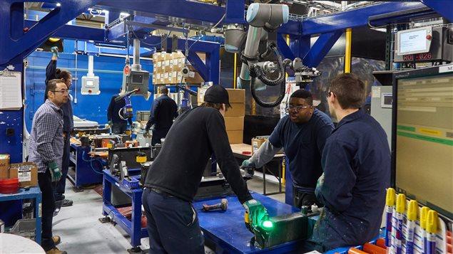 Des employés qui entourent des robots d'inspection chez Spectra Premium à Boucherville. Photo : Radio-Canada/Janic Tremblay