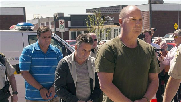 Former Montreal Maine and Atlantic Railway Ltd. employees Tom Harding, right, Jean Demaitre, centre, and Richard Labrie are escorted by police to appear in court in Lac-Megantic, Que., on Tuesday, May 13, 2014.