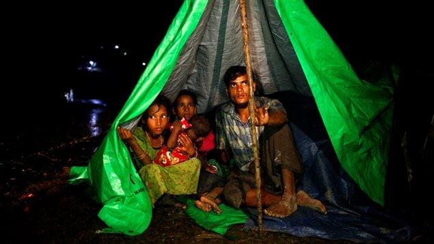 Rohingya refugees sit inside a makeshift tent near Gundum in Cox's Bazar, Bangladesh, September 3, 2017.