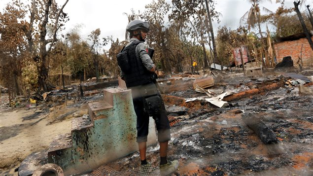 A police officer stands in a house that was burnt down during the days of violence in Maungdaw, Myanmar August 30, 2017.