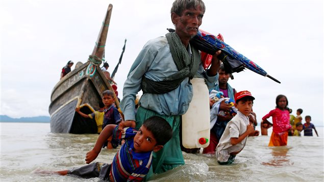 A Rohingya refugee man pulls a child as they walk to the shore after crossing the Bangladesh-Myanmar border by boat through the Bay of Bengal in Shah Porir Dwip, Bangladesh, September 10, 2017.