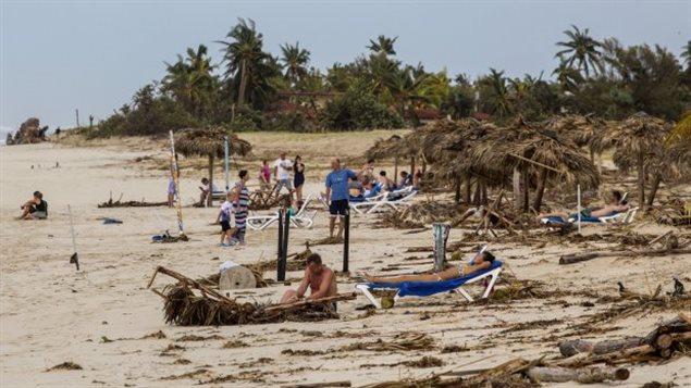 Les touristes se trouvent sur une plage, jonchés de palmiers, un jour après que l'ouragan Irma a passé au dessus de station balnéaire à Varadero à Cuba, le dimanche 10 septembre 2017. (AP Photo / Desmond Boylan)