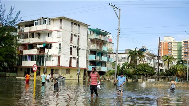 People walk in a flooded area after Hurricane Irma caused flooding and a blackout, in Havana, Cuba September 11, 2017.