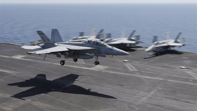 Super Hornet fighter jets are shown landing on the flight deck of the USS Theodore Roosevelt aircraft carrier. Canada says it is rethinking the 6.3 billion dollar purchase of 18 of the Boeing fighters in light of Boeing's trade complaint against Bombardier