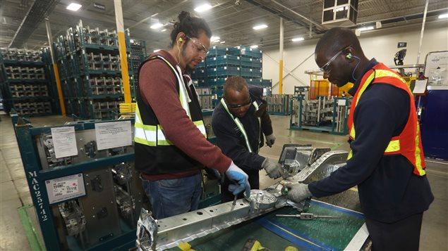 Des travailleurs vérifient les pièces d'automobiles soudées dans une usine.