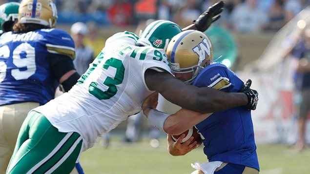Winnipeg Blue Bombers' Buck Pierce is sacked by Saskatchewan Roughriders' Tearrius George during the first half of their CFL game in Winnipeg Sunday, September 11, 2011