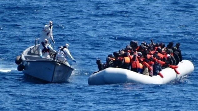 Italian navy personnel, left, approach a rubber dinghy filled with refugees in the Sicilian Channel in the Mediterranean Sea in March. There are new fears that up to 400 people are dead after their boat capsized in the Mediterranean in April 2016