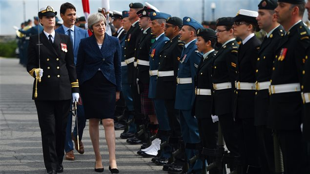 British Prime Minister Theresa May takes part in a troop inspection as she is greeted by Prime Minister Justin Trudeau to Parliament Hill in Ottawa on Monday, Sept. 18, 2017.