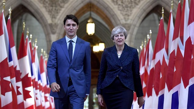 Prime Minister Justin Trudeau and British Prime Minister Theresa May walk in the Hall of Honour on Parliament Hill in Ottawa during a visit on Monday, Sept. 18, 2017.