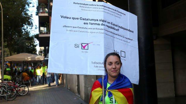 Una catalana con un cartel que ilustra una boleta con el voto por el