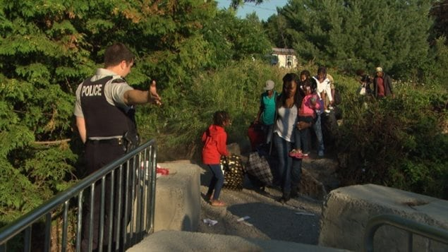 Asylum seekers cross into Quebec earlier this year. Canadian officials believe as many as 40,000 people will be seeking refuge before the end of 2017.