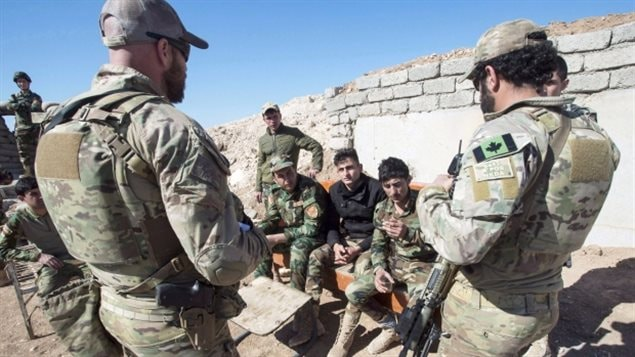Canadian special forces soldiers, left and right, speak with Peshmerga fighters at an observation post, in northern Iraq earlier this year. They will soon be joined in the country by a dozen Canadian army combat engineers who will train local security forces to detect and defuse roadside bombs.