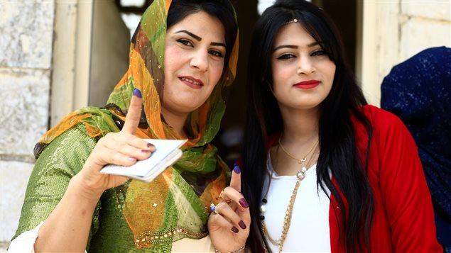 Dos mujeres kurdas muestran sus dedos marcados con tinta que señalan que votaron en el referéndum sobre la independencia de los kurdos en Kirkuk, Irak. 25 de septiembre de 2017.