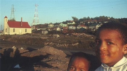 Two children pose in 2016 in front of what is left of Africville, a once-vibrant community in Halifax, Nova Scotia.
