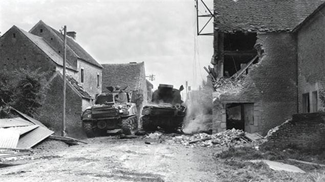 Another of Currie's handful of Sherman tanks moves past a disabled tank during the hard fought battle to take the town from a much bigger force of defenders.
