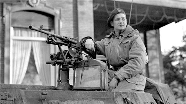Maj. D.C Currie leaning on a Bren gun, possibly sitting on an armourred recce vehicle