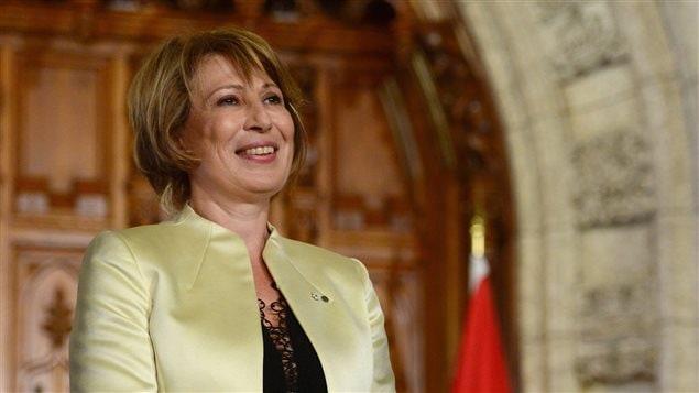 Mme Nemer sourit devant un drapeau canadien lors de la conférence de presse annonçant sa nomination