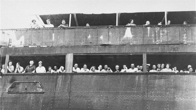 Jewish refugees aboard the MS St. Louis attempt to communicate with friends and relatives in Cuba, who were permitted to approach the docked vessel in small boats on June 3, 1939, just days before the vessel was denied entry to Canada.