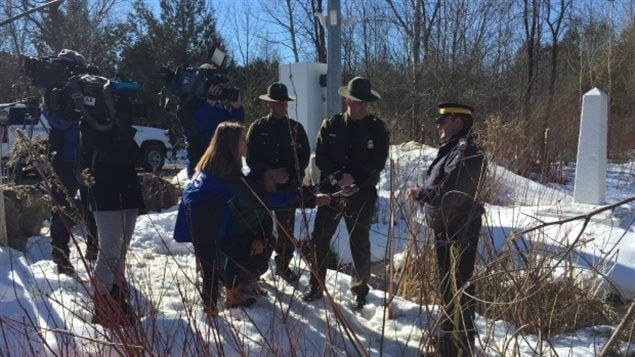 American reporters reached across the border last winter to interview an RCMP officer, right, while U.S. border agents looked on. Figures revealed Thursday the number of asylum seekers to Canada is up by more than 8,000  persons from all of 2016.