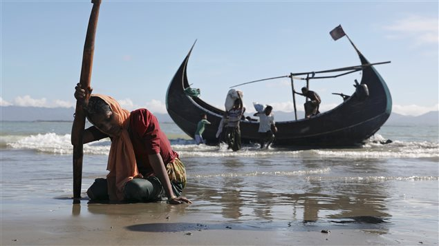 A woman collapses from exhaustion as Rohingya refugees arrive by a wooden boat from Myanmar to the shore of Shah Porir Dwip, in Teknaf, near Cox's Bazar in Bangladesh.