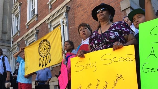 Supporters of the Sixties Scoop hold signs and flags outside a Toronto courthouse during a rally in 2016.