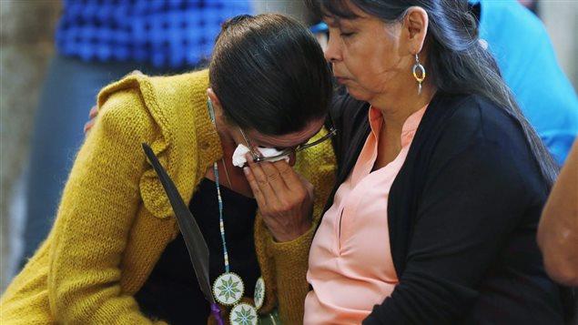 Une femme est réconfortée lors d'un rassemblement des victimes de la rafle des années 1960 avant une excuse provinciale, au Manitoba, en juin 2015. Photo : La Presse canadienne/John Woods