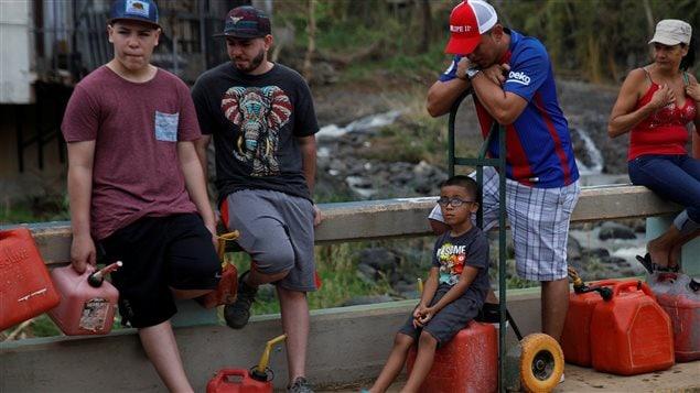 Puertoriqueños hacen cola para comprar gasolina.