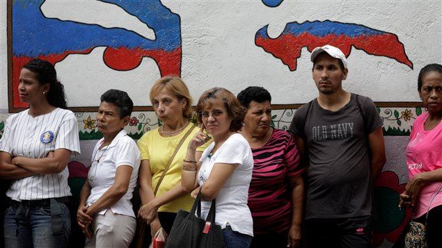 Ciudadanos hacen fila para votar en Caracas este domingo 15 de octubre.