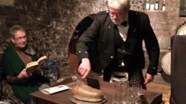 David Allison of the St. Andrew's Society in St John's Newfoundland cuts the haggis at a Robbie Burns celebration in 2015