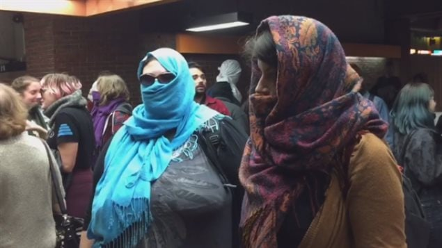 Non-Muslims in Montreal covered their faces and entered the subway to protest a new law that bans face-coverings for anyone accessing or providing public services.