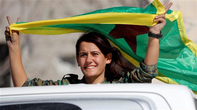 """مقاتلة من """"قوات سوريا الديمقراطية"""" ترفع علم """"وحدات حماية الشعب"""" الكردية (YPG) في مدينة الرقة في 18 تشرين الأول (أكتوبر) الجاري غداة السيطرة الكاملة لهذه القوات على المدينة التي كانت تُعتبر عاصمة تنظيم """"الدولة الإسلامية"""" (""""داعش"""") في سوريا."""