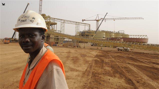 Un travailleur devant le chantier de construction de la mine d'or Essakane, la plus grande mine d'or du pays. Plusieurs sociétés minières du Canada ont acquis des droits minières au Burkina Fasso.