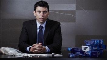 Le professeur David Hammond, assis à son bureau avec les paquets de cigarettes
