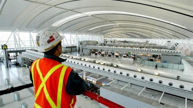 Aecon Construction scissor lift operator, Abel Sousa, looks at Toronto Pearson International Airport's new Terminal 1 check-in area from above the scissor lift on Dec. 2, 2003.