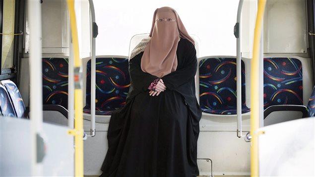 Une résidente de Montréal, Warda Naili, porte le niqab, voile intégral dans un autobus de la ville le 21 octobre 2017.
