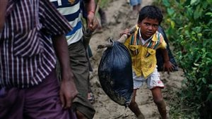 A Rohingya refugee boy carries his belongings as he walks to a makeshift camp in Cox's Bazar, Bangladesh September 18, 2017.